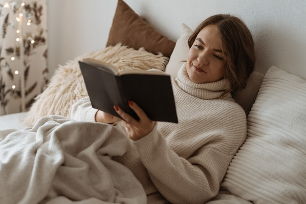 Cozy autumn winter day. woman reading book. comfy lifestyle