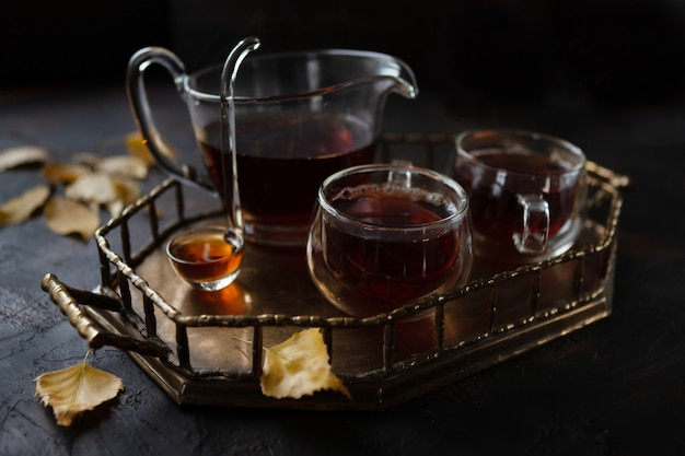 Cozy autumn with two mugs and  jug with hot tea on  metal tray and yellow autumn leaves