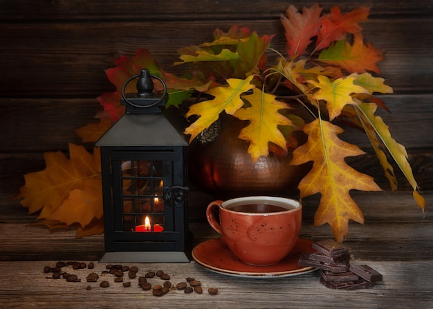 Cozy autumn with yellow leaves, lantern, hot coffee cup coffee beans and chocolate