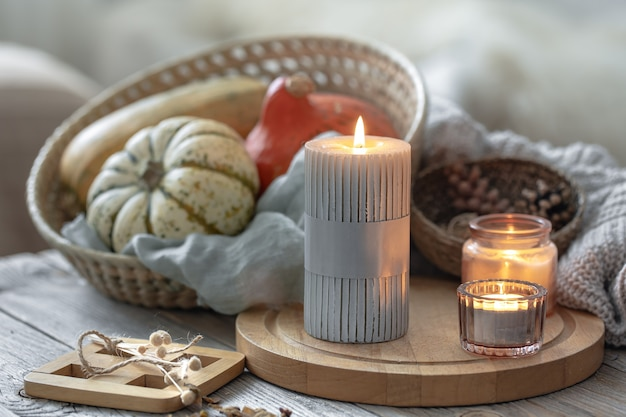 Cozy autumnal composition with burning candles and pumpkins on a blurred background.