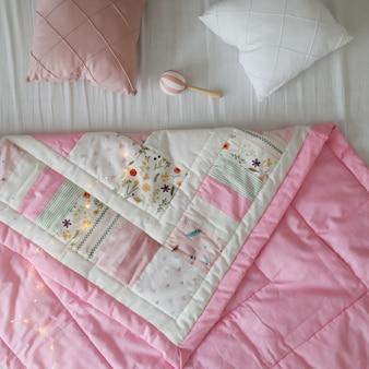 パッチワーク毛布付きの居心地の良いベビーベッド