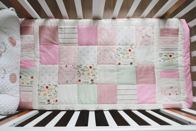 Уютная детская кроватка с розовым пледом в стиле пэчворк, детское постельное белье и текстиль для сна и сна в детской.