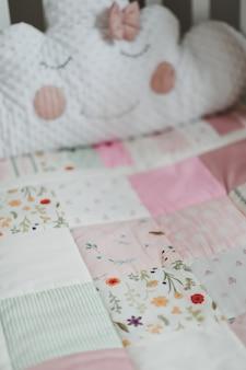 Уютная детская кроватка с розовым пледом в стиле пэчворк