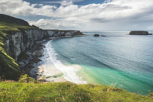 Уютная бухта рядом с берегом северной ирландии, покрытая травой скала, омываемая бирюзовым морем.