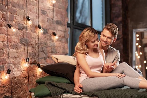 居心地の良い寝室。居心地の良い寝室で夜を過ごしながら、ほっとする陽気なカップル
