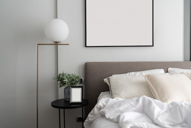 Cozy bedroom corner with modern brown fabric bed headboard and comfortable pillows  setting with gold lamp and artificial plant in glass vase on side table