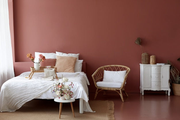 レトロなアームチェア、ヴィンテージのチェストドワーフ、ベッドの居心地の良いベッドルームのインテリア