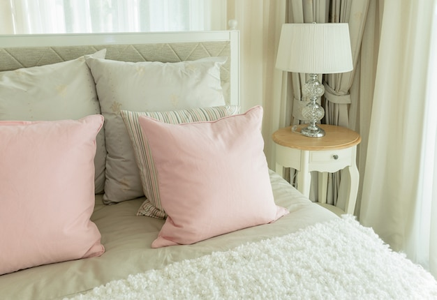 Cozy bedroom interior with pink pillows and reading lamp on bedside table