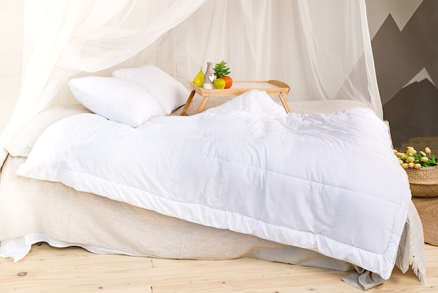 A cozy bedroom in pastel colors with a wooden floor, a large four-poster bed, tray with fr