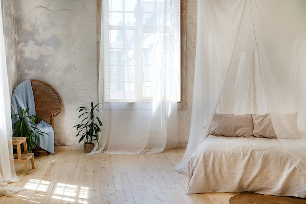 A cozy bedroom in pastel colors with a wooden floor, a large four-poster bed