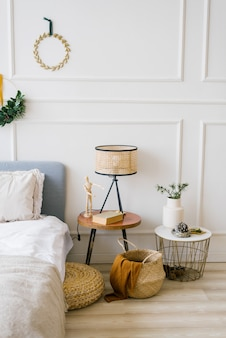 Cozy bedroom with a bed and a christmas wreath, bedside table