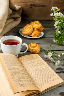春または初秋のお茶、焼きたてのスコーン、フィールドのデイジーと魅力的な本の花束で心地よい朝食。コピースペース
