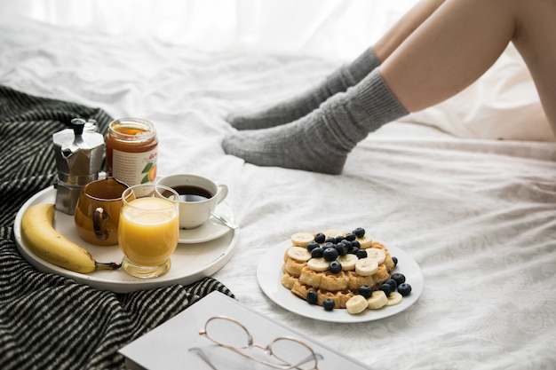 Cozy breakfast scene in bed on a weekend with coffee and waffles