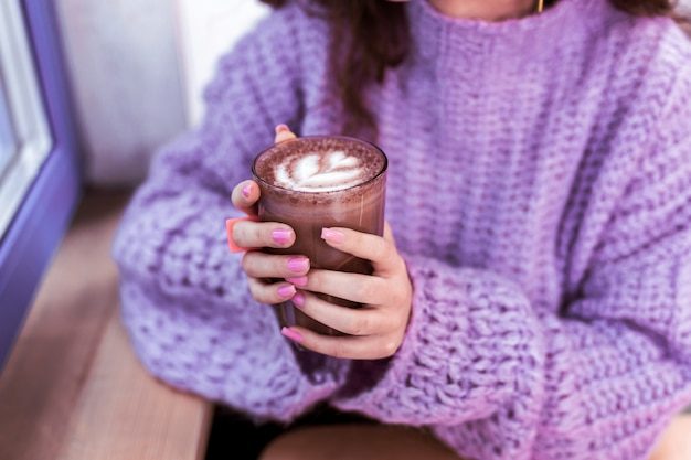 Cozy cafe. woman in knitted thick sweater holding glass of hot cacao with tidy hands with pink nails