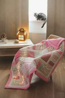 Уютное кресло с пледом спицами и забавным котиком