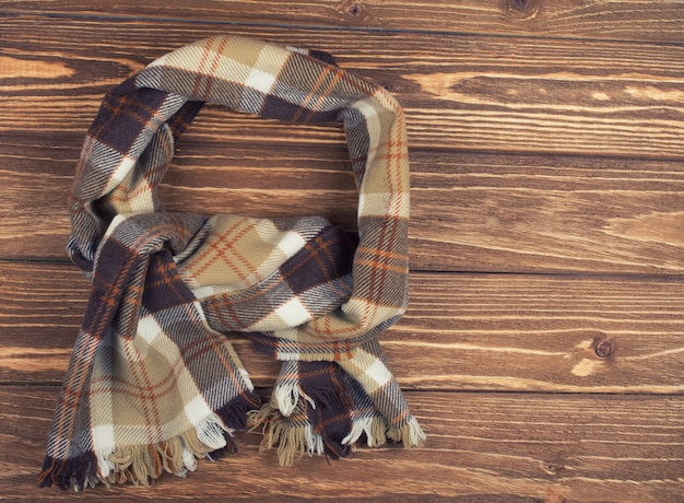 Cozy checkered scarf on a brown wooden background