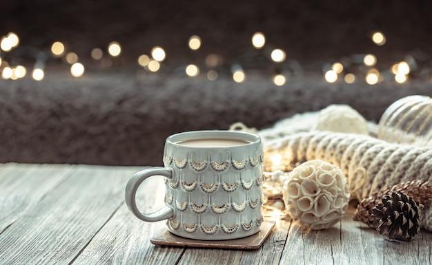 ボケ味のぼやけた背景に美しいカップと装飾の詳細を持つ居心地の良いクリスマスの背景。