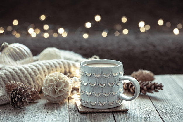 Cozy christmas background with a beautiful cup and decor details on a blurred background with bokeh.