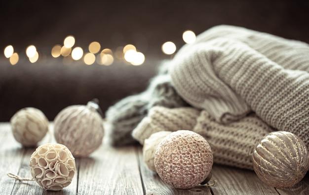 ぼやけた背景にクリスマスの装飾とニットの要素を持つ居心地の良いクリスマスの背景。