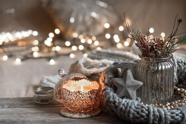 Уютная новогодняя композиция с зажженными свечами в декоративном подсвечнике. понятие домашнего уюта и тепла.