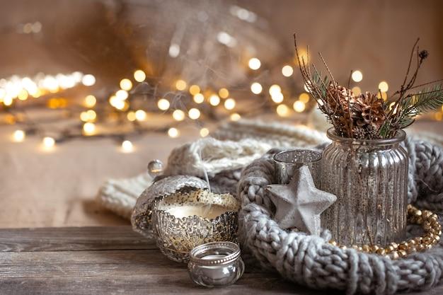 Уютная новогодняя композиция со свечами в декоративном подсвечнике. понятие домашнего уюта и тепла.