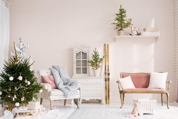 크리스마스 트리와 베개가있는 소파가있는 거실의 아늑한 크리스마스 장식. 스키는 벽에 서 있습니다. 새해 집안의 어린이 방의 고전적인 디자인