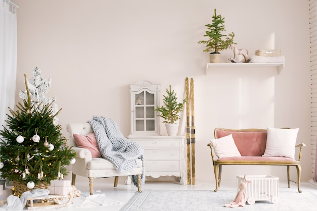 Cozy christmas decor in the living room with a christmas tree and a sofa with pillows. skis stand against the wall. classic design of a children's room in the house for the new year