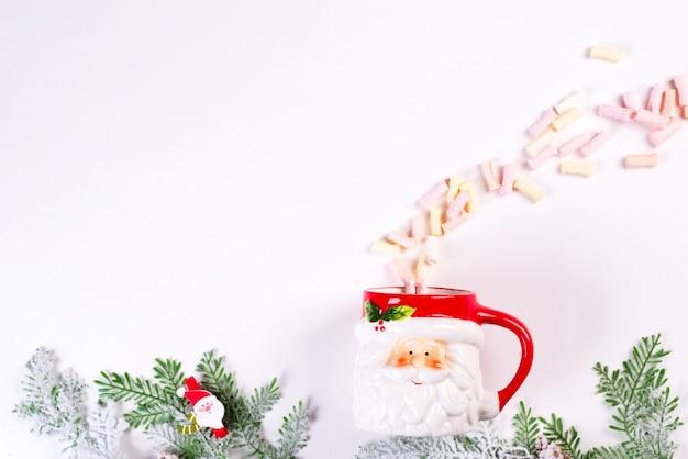 居心地の良いクリスマス休暇。クリスマスのおもちゃ、緑のモミの枝、白いテーブルにふわふわのマシュマロとサンタクロースのカップ。平置き