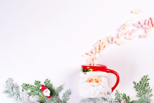 Cozy christmas holiday . christmas toys, green fir branches, santa claus cup with fluffy marshmallow on a white table. flat lay