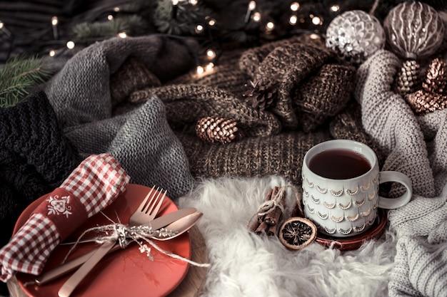 ベッドでお茶を飲みながら居心地の良いクリスマスの朝。セーターのある静物シーン。ホットコーヒー、お茶の蒸しカップ。クリスマスのコンセプト。