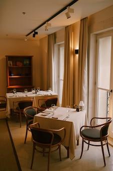 Уютный классический интерьер ресторана: столики у окна.