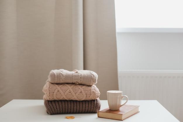 Уютная комфортная осенне-зимняя домашняя атмосфера и натюрморт с чашкой, подсвечником и свитерами.