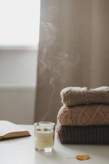Уютный уютный домашний осенний натюрморт со свечой, книгой, вязаными кофточками и пледом