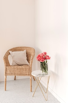 Cozy comfortable home rest space with rattan chair, white wall, mosaic tile, marble table with beautiful peony flower bouquet, pillow