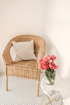 Cozy comfortable home rest space with rattan chair, white wall, mosaic tile, marble table with beautiful peony flower bouquet