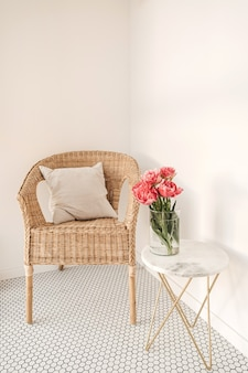 Cozy comfortable home rest space with rattan chair, white wall, mosaic tile, marble table with beautiful peony flower bouquet.