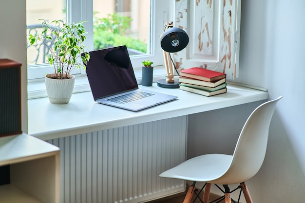 Cozy comfortable homely workplace by the window in a white interior