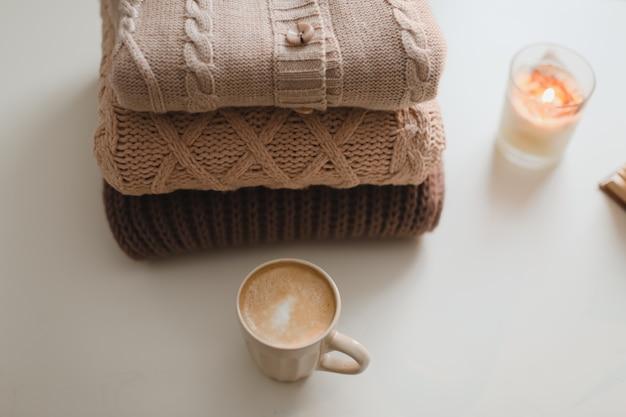 居心地の良い快適なヒュッゲの家庭的な雰囲気とカップキャンドルとセーターのある静物