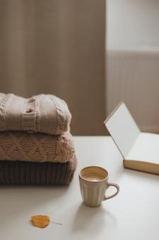 Уютная комфортная зимняя и осенняя домашняя атмосфера и натюрморт с чашкой и тёплыми свитерами.