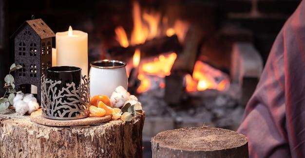 燃える暖炉のコピースペースのカップ、キャンドル、みかんを備えた居心地の良い構成。