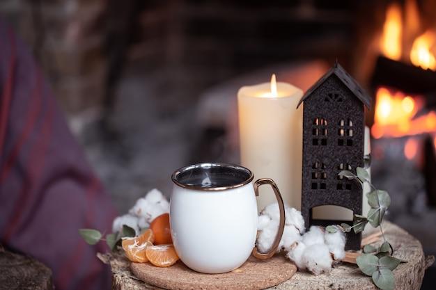 Уютная композиция с чашкой, свечой и мандаринами на размытом фоне копировального пространства горящего камина.