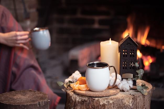 Уютная композиция с чашкой, свечой и мандаринами с копией горящего камина.