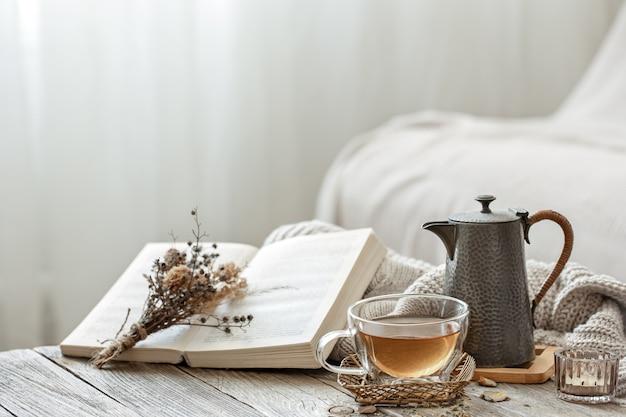 ぼやけた背景の部屋の内部にお茶と本を置いた居心地の良い構図。