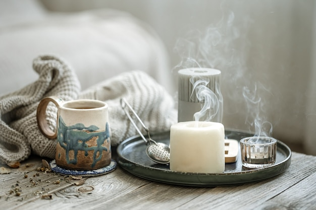 Cozy composition with a ceramic cup, candles and a knitted element on a blurred background.