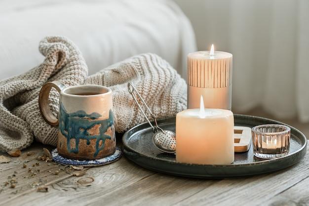 Accogliente composizione con una tazza in ceramica, candele e un elemento in maglia