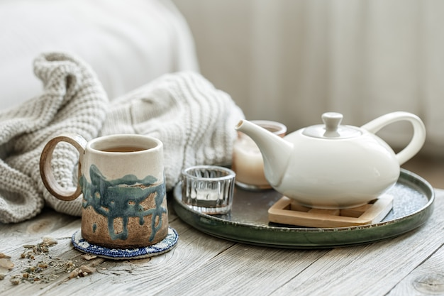Cozy composition with a ceramic cup, a teapot and a knitted element on a blurred background.