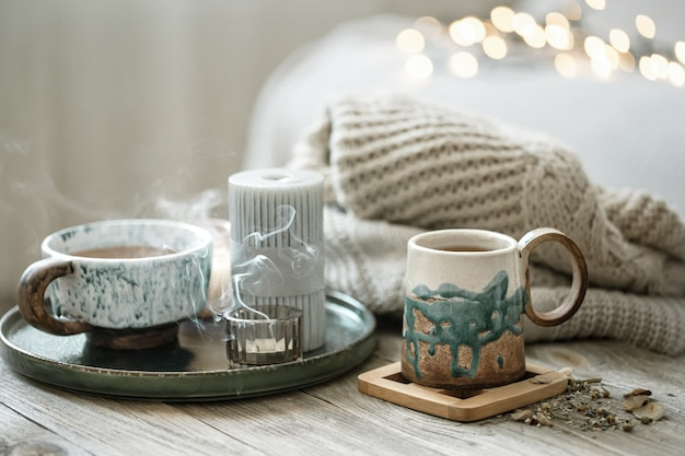 Cozy composition with ceramic cups and candles on a blurred background with bokeh.