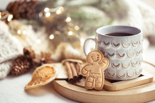 Cozy composition with a christmas cup with hot drink and gingerbread. home winter coziness concept.