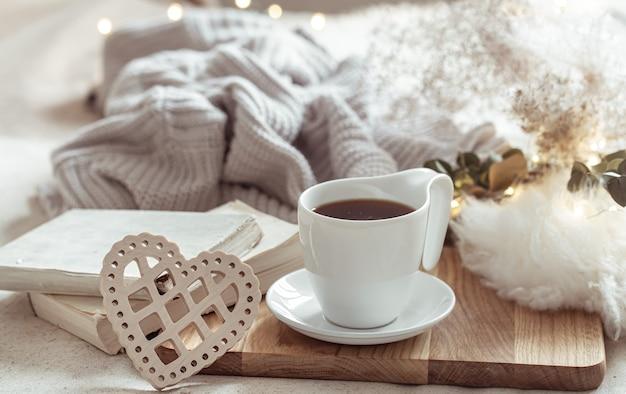 Accogliente composizione con tazza di caffè su piattino e dettagli home decor.