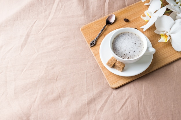 Cozy composition with a cup of coffee on a tray with sugar on a pastel coffee blanket flat lay, top view.
